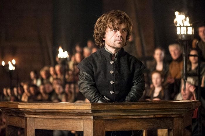 Tyrion Lannister stands in a courtroom wearing handcuffs