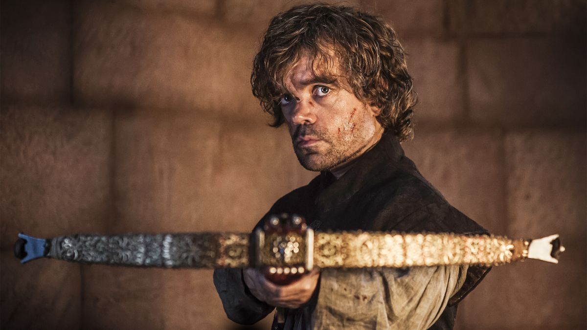 Tyrion Lannister holds a crossbow that is pointed at Tywin (off camera)