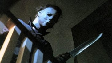 Michael Myers looking down while wielding a knife.