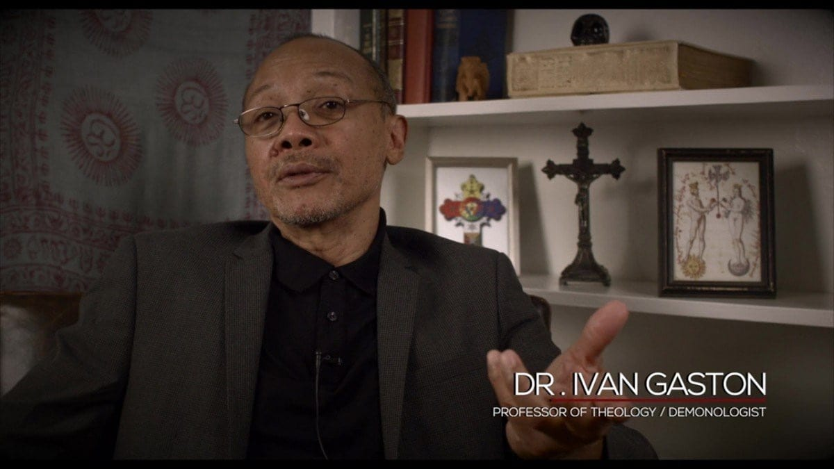 Picture of a middle-aged man sitting in front of a wall of shelves with various occult-themed items on them. Caption states his name is Dr. Ivan Gaston, progessor of theology and demonologist