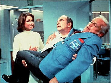 Lou Grant carries Ted Baxter after passing out