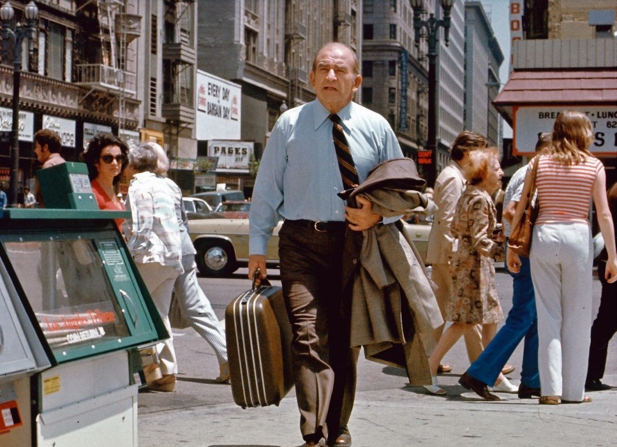 Lou walks down the street with a suitcase