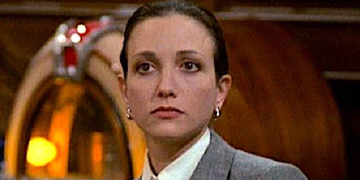 Lilith Sternin looking ahead wearing a serious expression with a jukebox in the background in Cheers