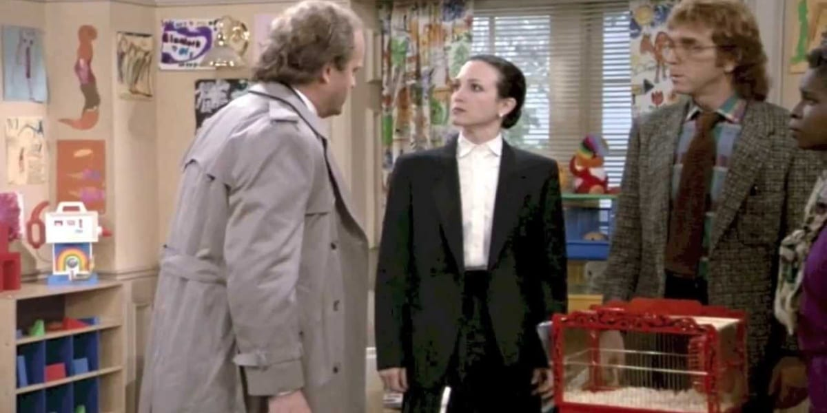 Frasier with his back to the camera, with Lilith standing before him looking up at his face in anger, and a bewildered man to Lilith's left in Cheers