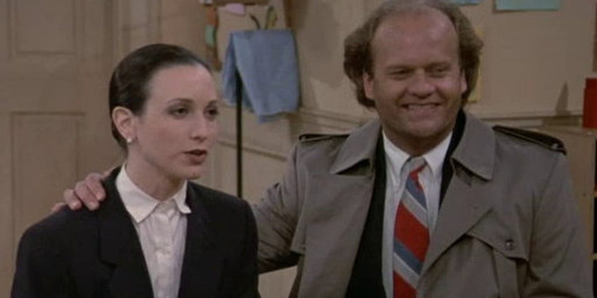 Frasier smiling with an arm around Lilith, who looks polite but annoyed in Cheers