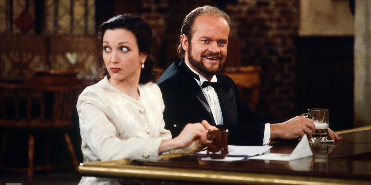 Frasier smiling at the bar and Lilith looking over her shoulder behind her sitting at the bar in Cheers