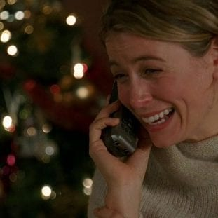 Penny holds a phone to her ear while standing in front of a Christmas tree