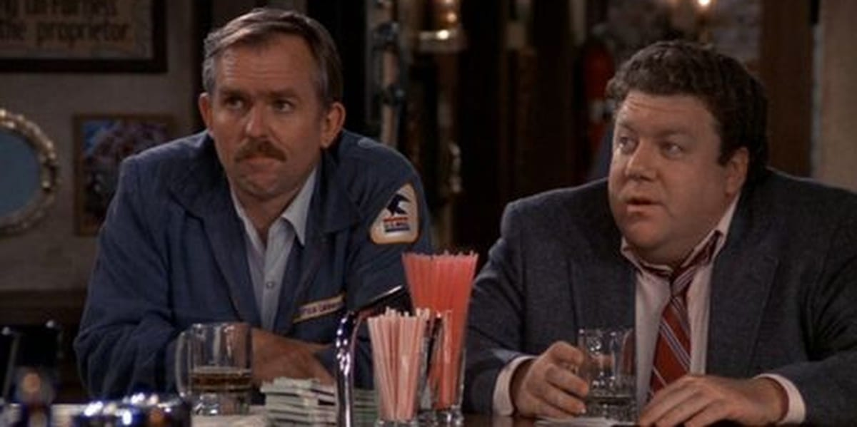 Cliff and Norm sitting at the bar and looking to their right in Cheers