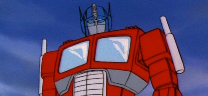 The big red truck with a blue robot head, Optimus Prime, stands heroically before the camera.