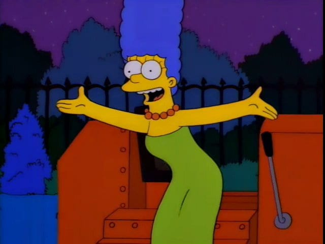 Marge stands in front of a bulldozer, singing