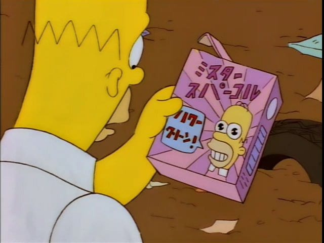 "Homer looks at the ""Mr. Sparkle"" box with his face on it"