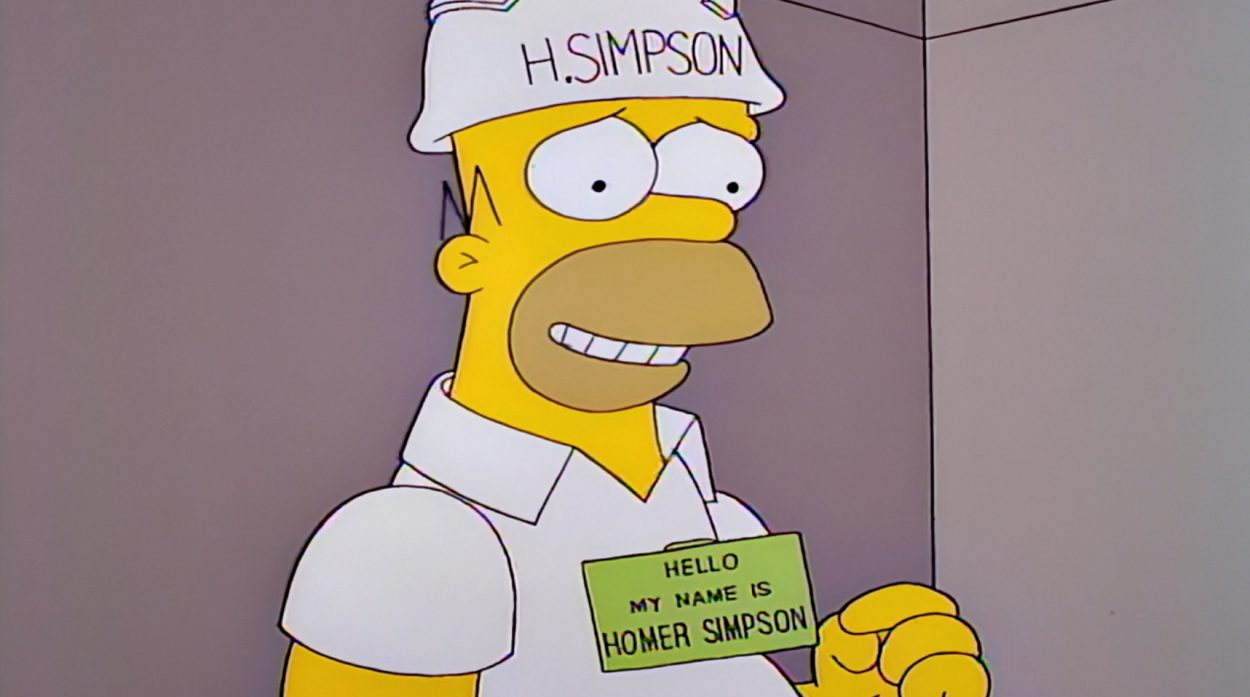 Homer wearing a hardhat with H. Simpson on it and a nametag