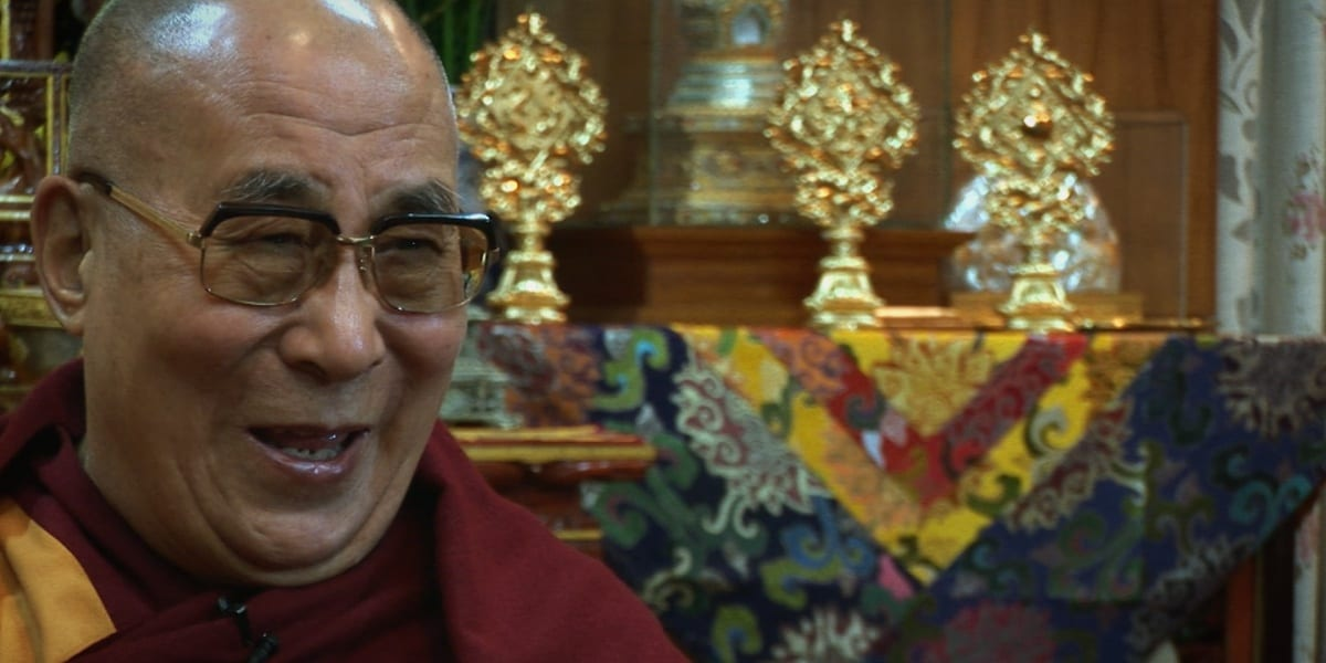 Dalai Lama smiling with table cloth and gold figures in background