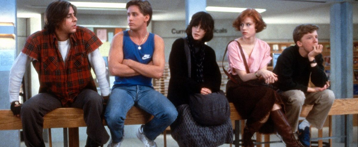 The Cast of the Breakfast Club sitting on a railing looking at one another