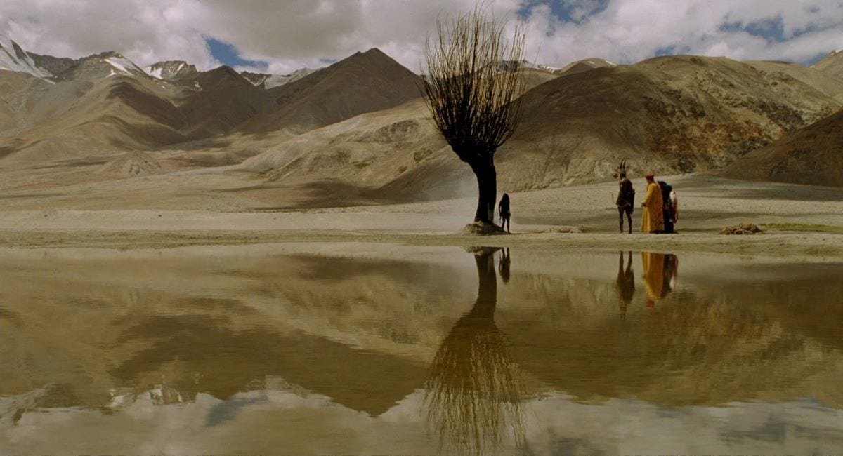 The bandits gather around the tree birthing a shaman in the desert in a fantasy sequence from The Fall