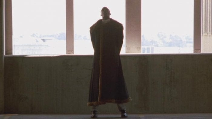 Candyman stands in a low lit parking garage with his hands behind his back.