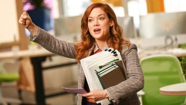 Zoey holds her paperwork but raises a fisted arm into the air to feign confidence.