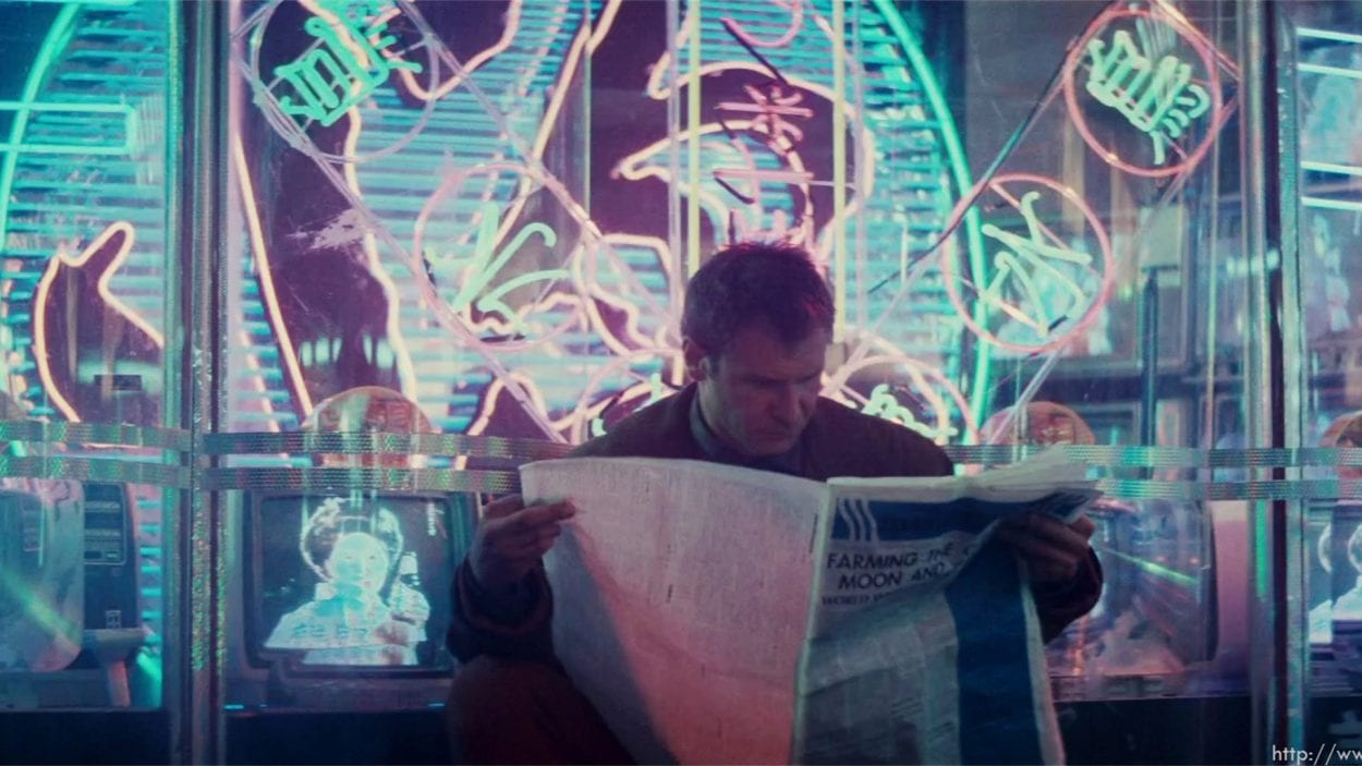 Harrison Ford reading a newspaper in Blade Runner with Neon lights behind him