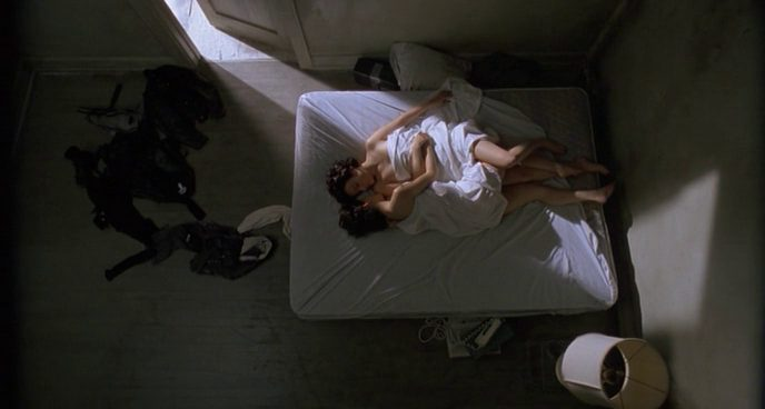 Two women in a bed with a white sheet covering them