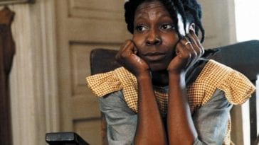 Whoopi Goldberg in 1920s dress, sits with her hands on her face.