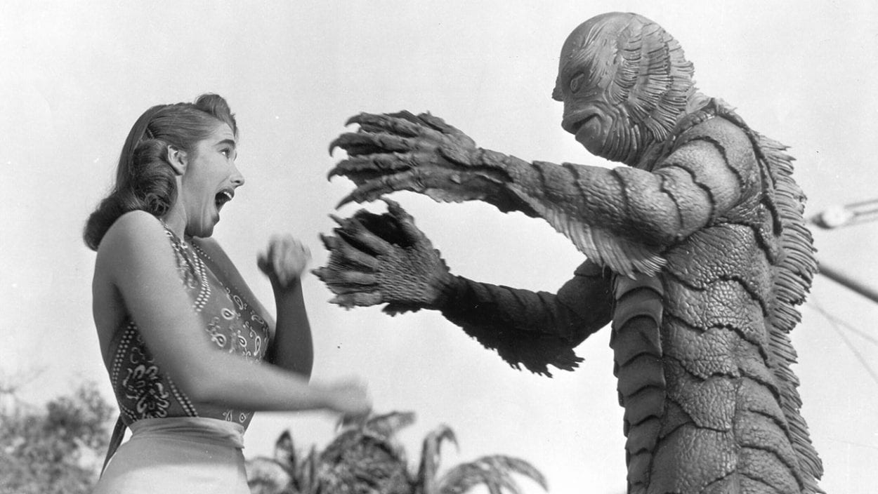 Black-and-white still of monstrous Gill Man reaching clawed, webbed fingers out to a screaming white woman.