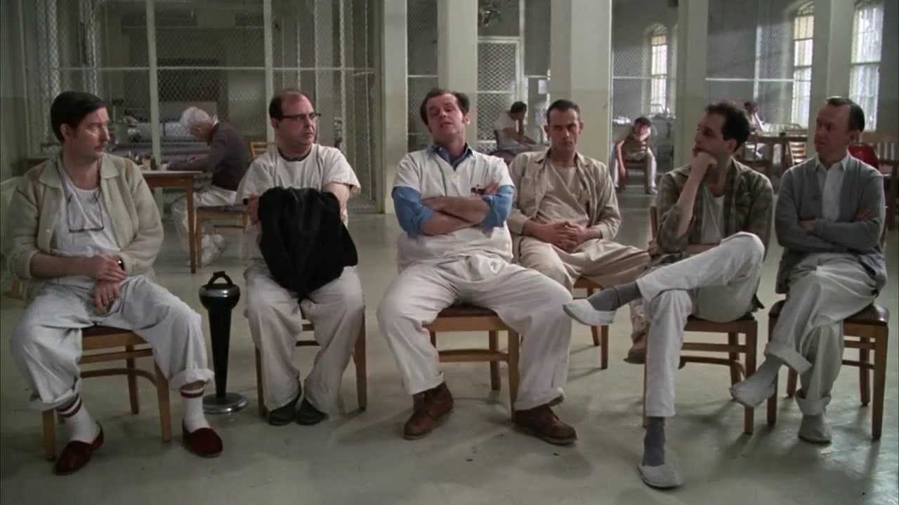 the men of the ward sit discussing their difficulties on the psych ward, with McMurphy seated center