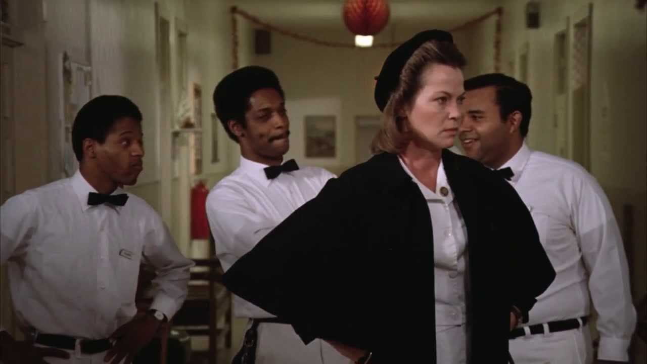 Nurse Ratched stands with her hands on her hips while 3 black male orderlies smirk behind her back