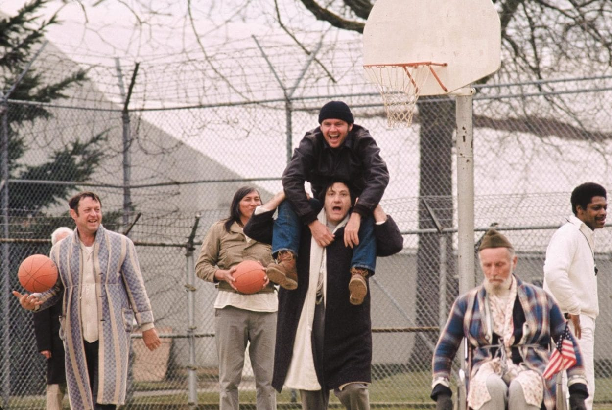 McMurphy sits on the shoulders of another patient as they play basketball