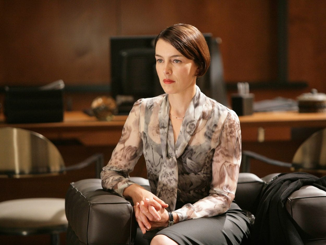 Adelle DeWitt sits in an armchair in an office, hands clasped.