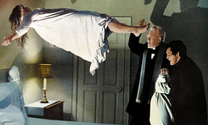 A priest tries to exorcise a demon from a levitating young girl
