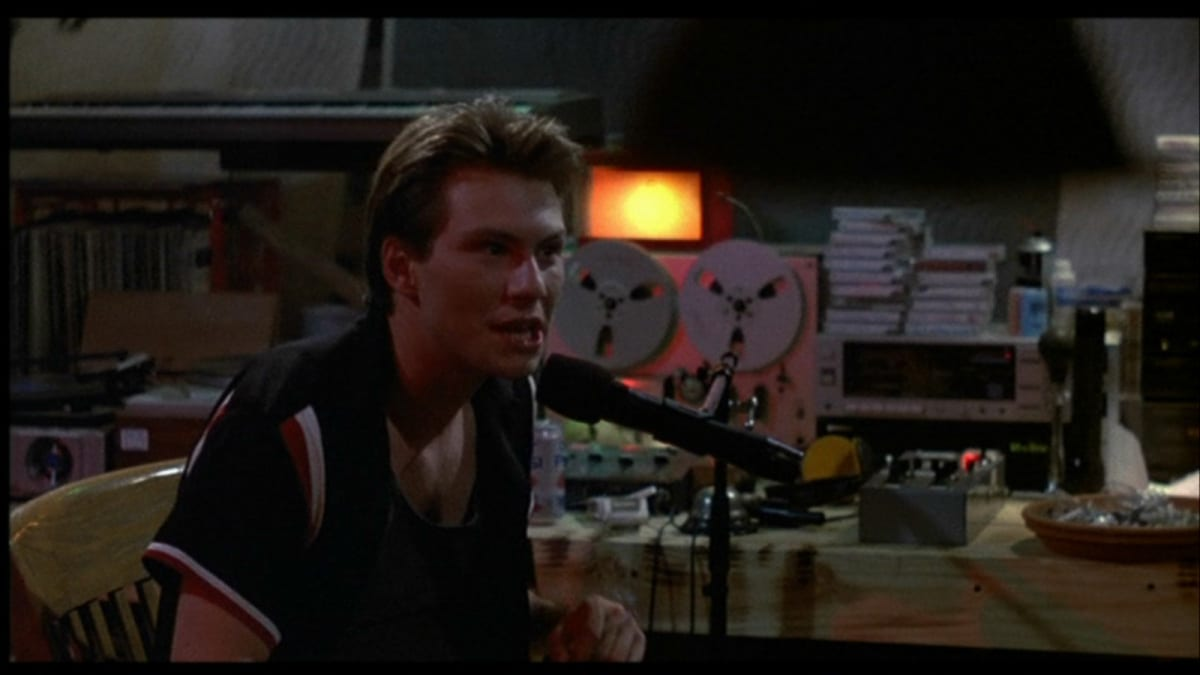 Christian Slater, talking into a microphone like a radio DJ