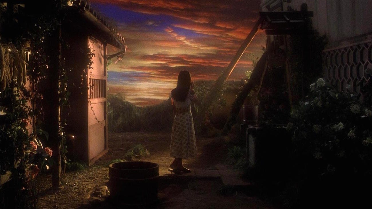 The character of Fantasy admires the painted sky as she stands next to the well.