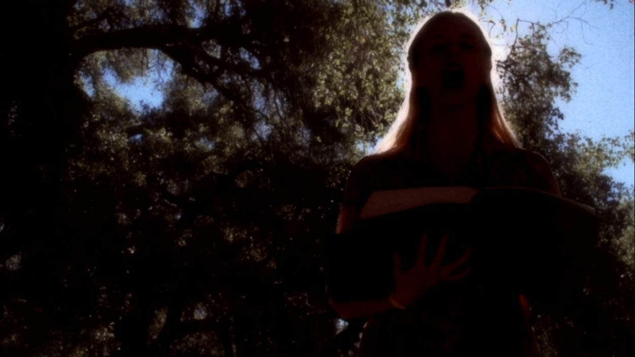 Screenshot of a girl holding a large leather bound book, standing under some trees in the forest. Camera is angled up at her face and she is heavily back lit to the point of silhouette