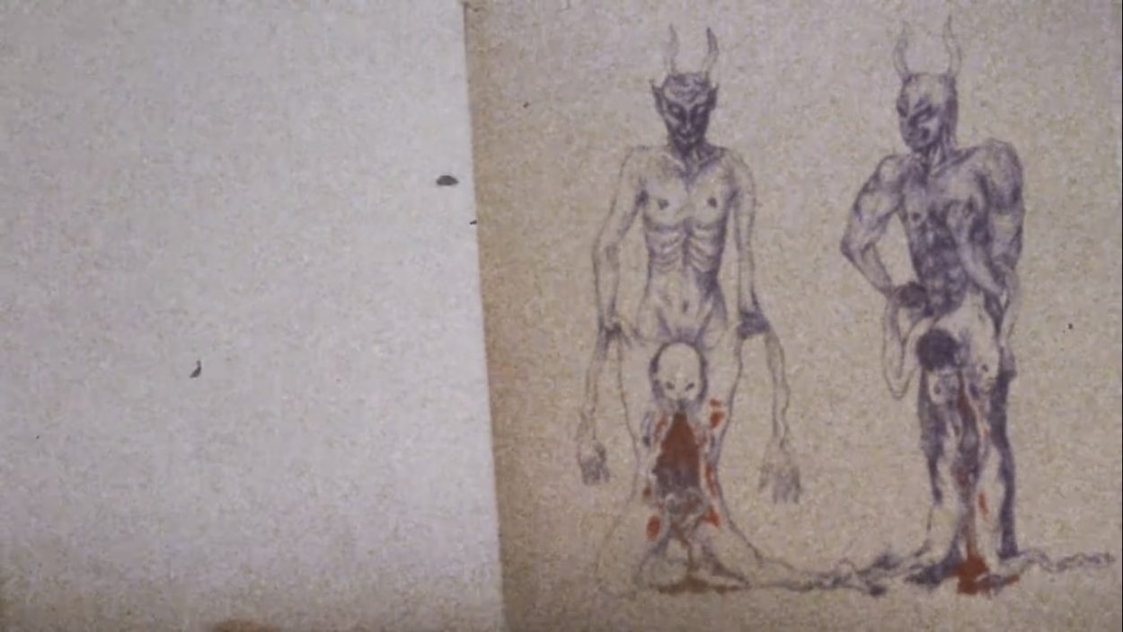 Illustration in a book of two horned devils gripping the bloody, sagging skins of two humans