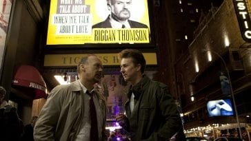 Riggan and Mike talk on the street beneath a theatre marquee.