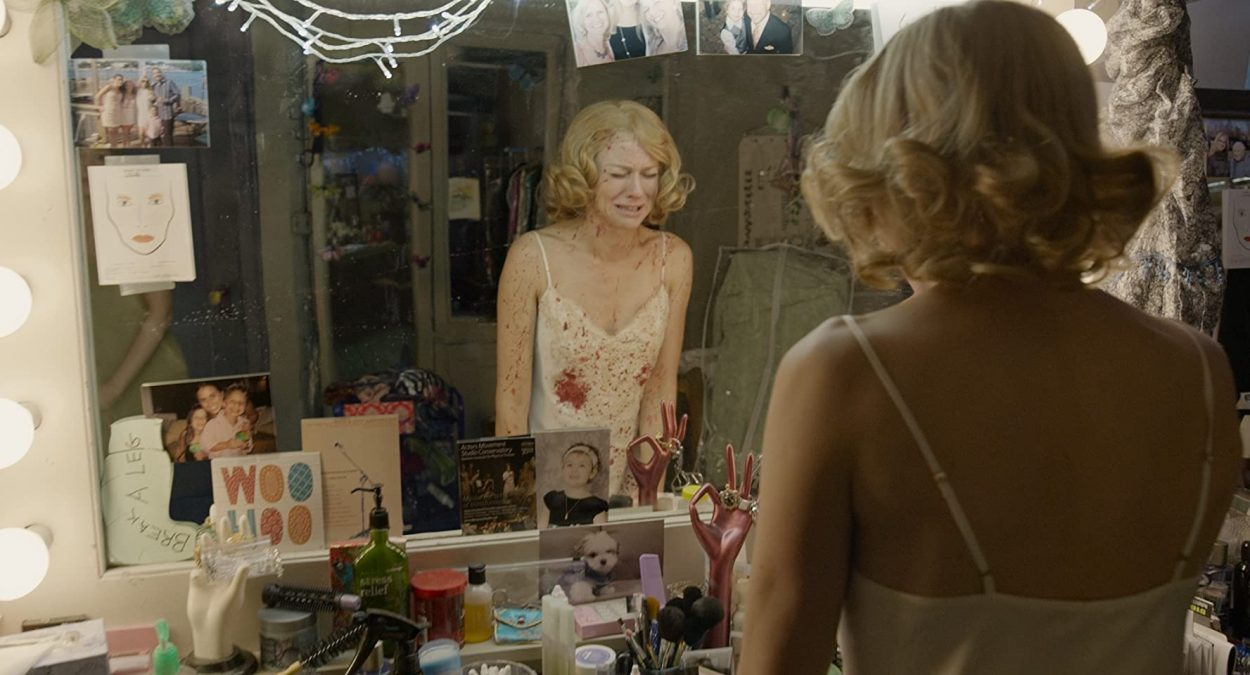 Leslie wears a blood-splattered negligee and sobs in her dressing room mirror.