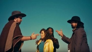 "A scene from the music video for ""Future Peg"" shows Man Man singer Honus Honus and a man in a poncho pointing finger pistols at one another while a man and woman stand between them."