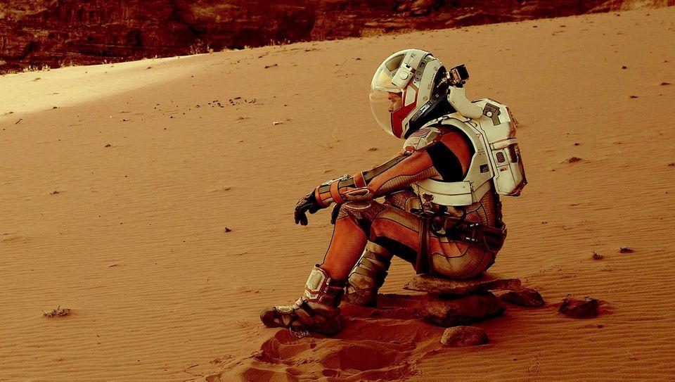 Matt Damon in The Martian sitting on Mars in a spacesuit