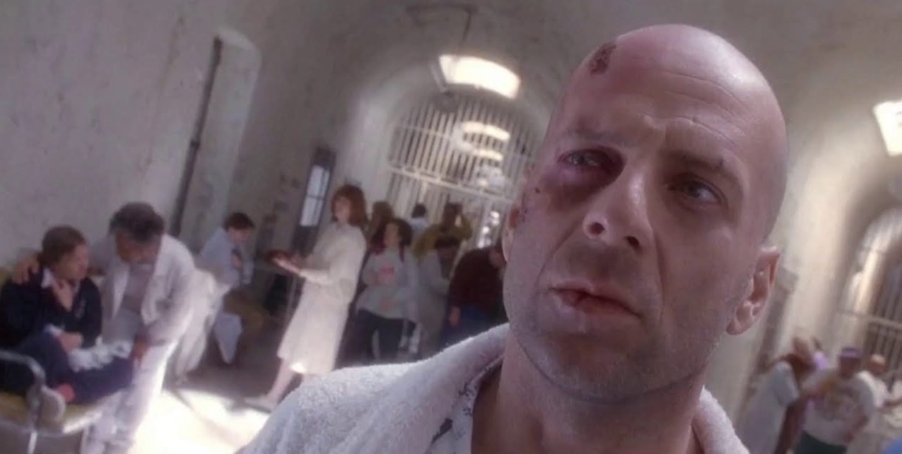 James Cole (Bruce Willis) puzzlingly looks offscreen in a psychiatric hospital