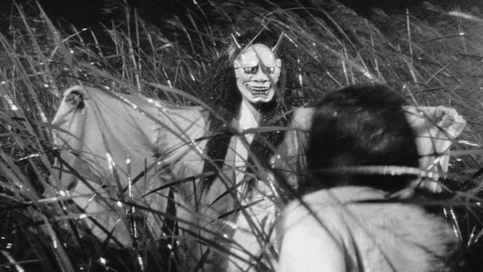 The mother-in-law, in flowing robe, wearing the long-haired, horned, big-eyed demon mask, spreads her arms as she appears from out of the wet, windblown reeds to terrify her daughter-in-law, seen from behind in the foreground.