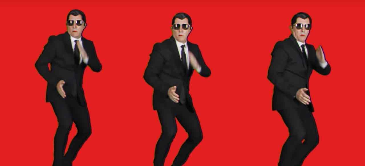 "Three Maynards dance in black suits against a red background in Puscifer ""Apocalyptical"""
