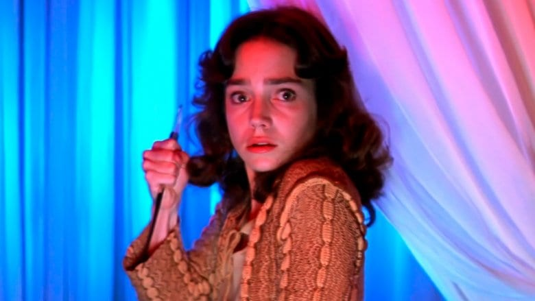 Suzy Bannion looks terrified and raises a knife in self defence in Suspiria