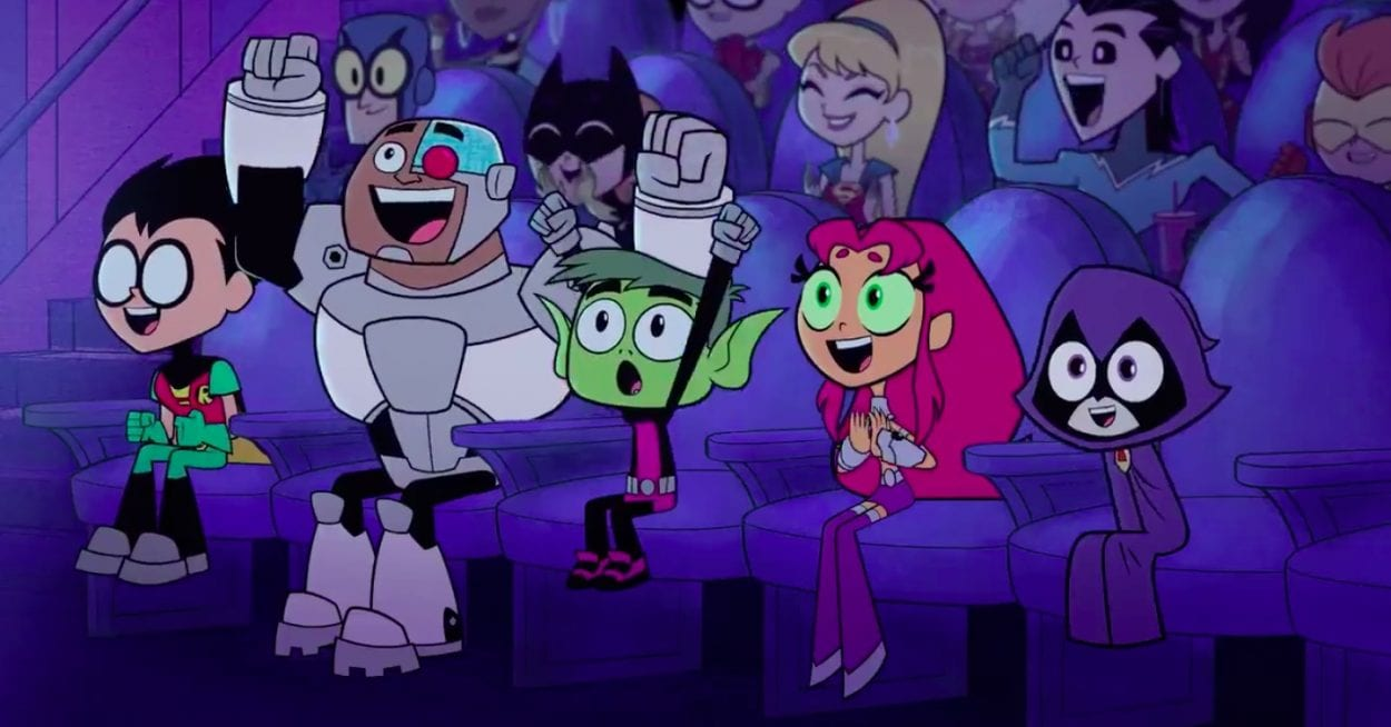 Robin, Cyborg, Beast Boy, Starfire and Raven cheer in a moovie theater filled with fellow superheroes.