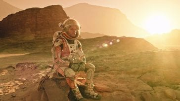 Matt Damon in The Martian sits on a rock on Mars