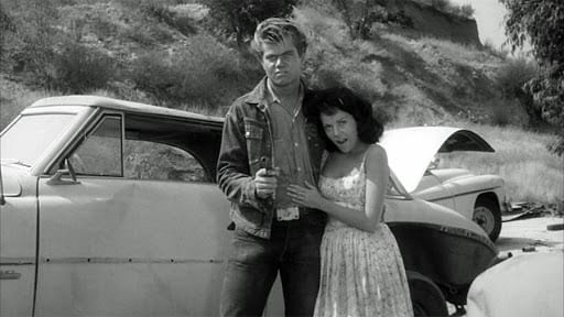 The titular sadist, clad in denim, gun in hand and his dark-haired girlfriend, wearing a white dress, stand next to each other amongst broken down cars.