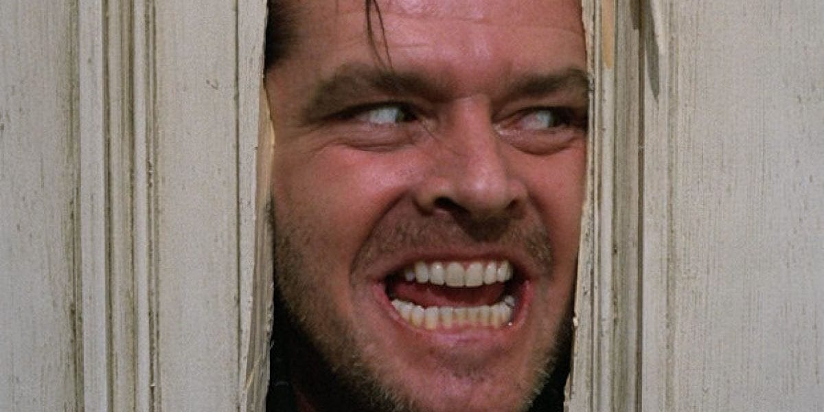 Jack Torrance peers through a broken door with a crazed look on his face