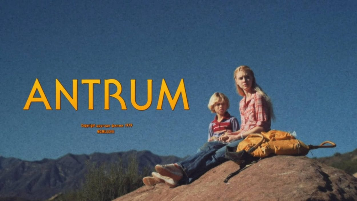 Screenshot showing The title Antrum and a young boy and his older sister sitting on top of a rock ledge with mountains visible in the background