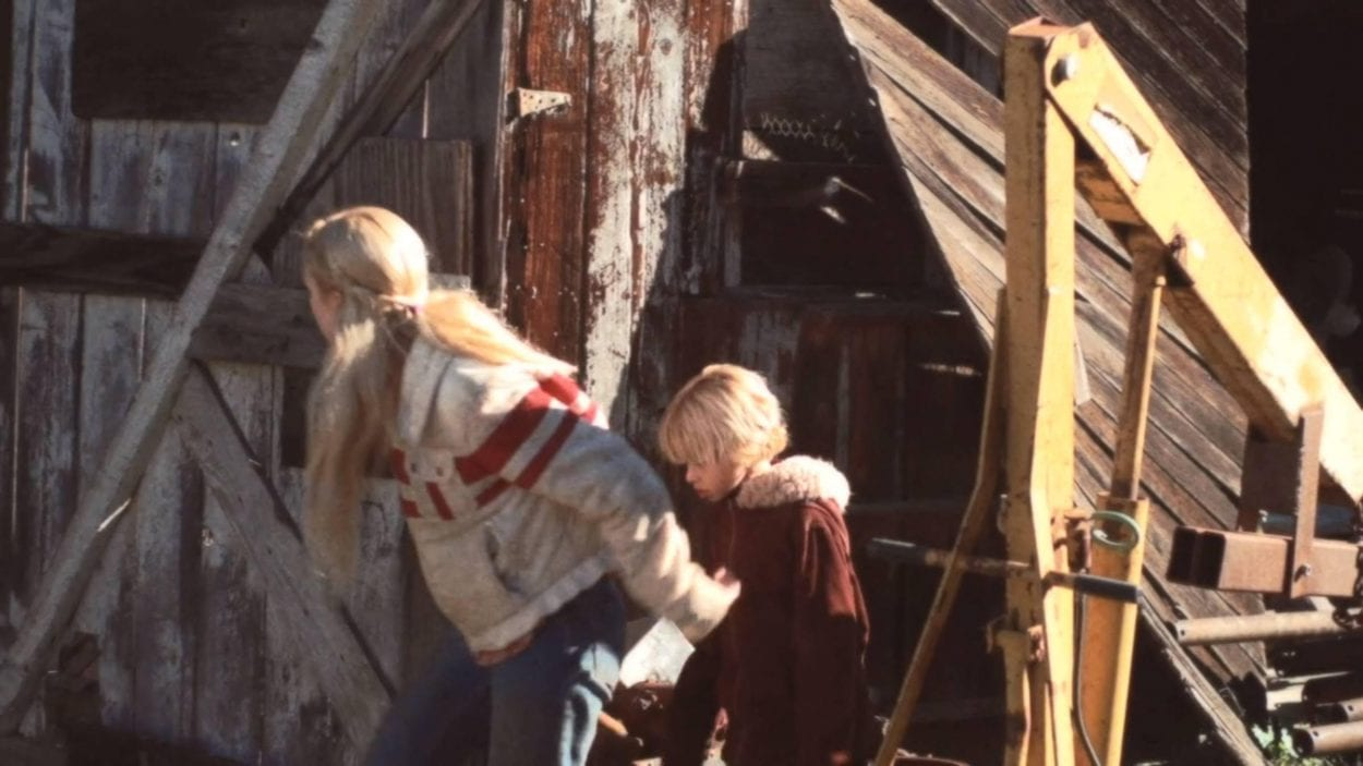 Blond Teenage girl and her young brother peering around the corner of some sort of barn or shed structure with various machinery nearby