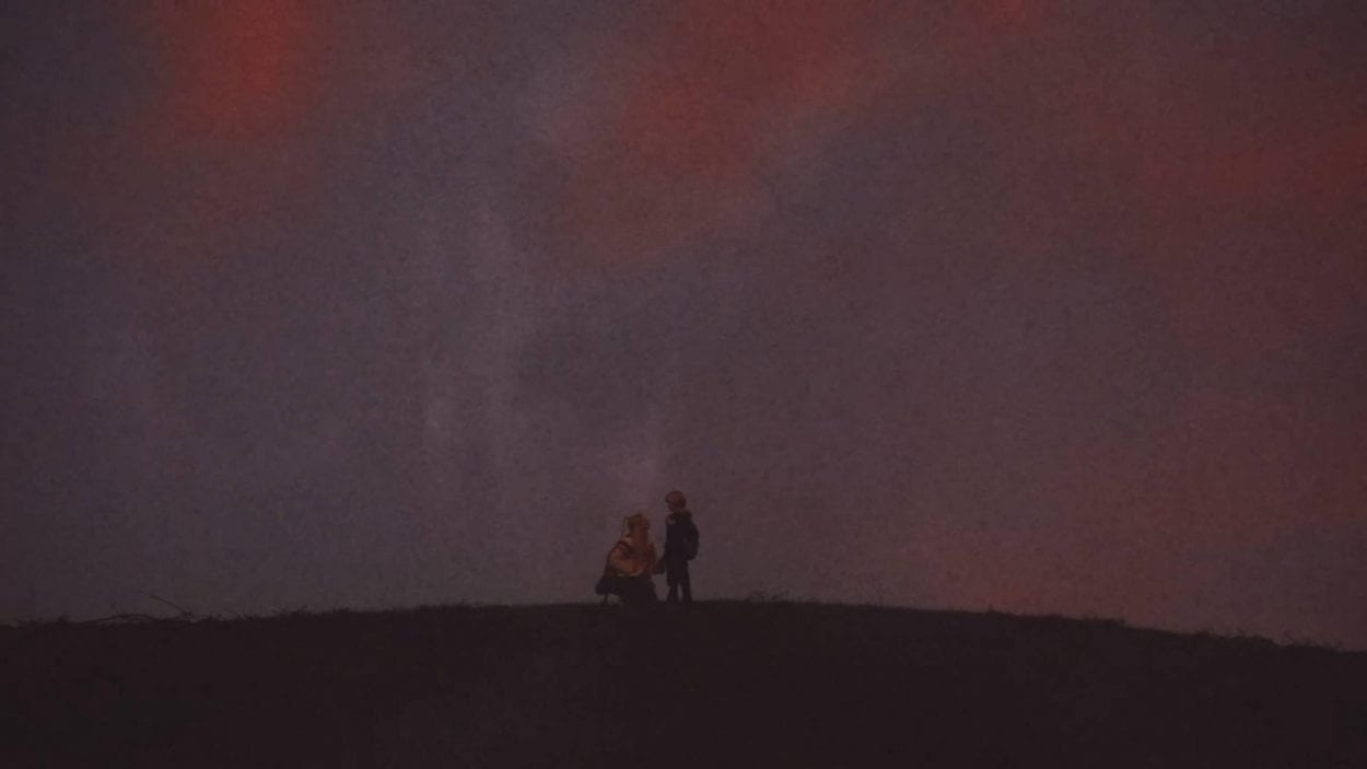 Teenage girl and younger brother standing on a hilltop - silhouetted against the purple dusk sky - the ghostly image of a giant horned devil is visible filling the sky over them