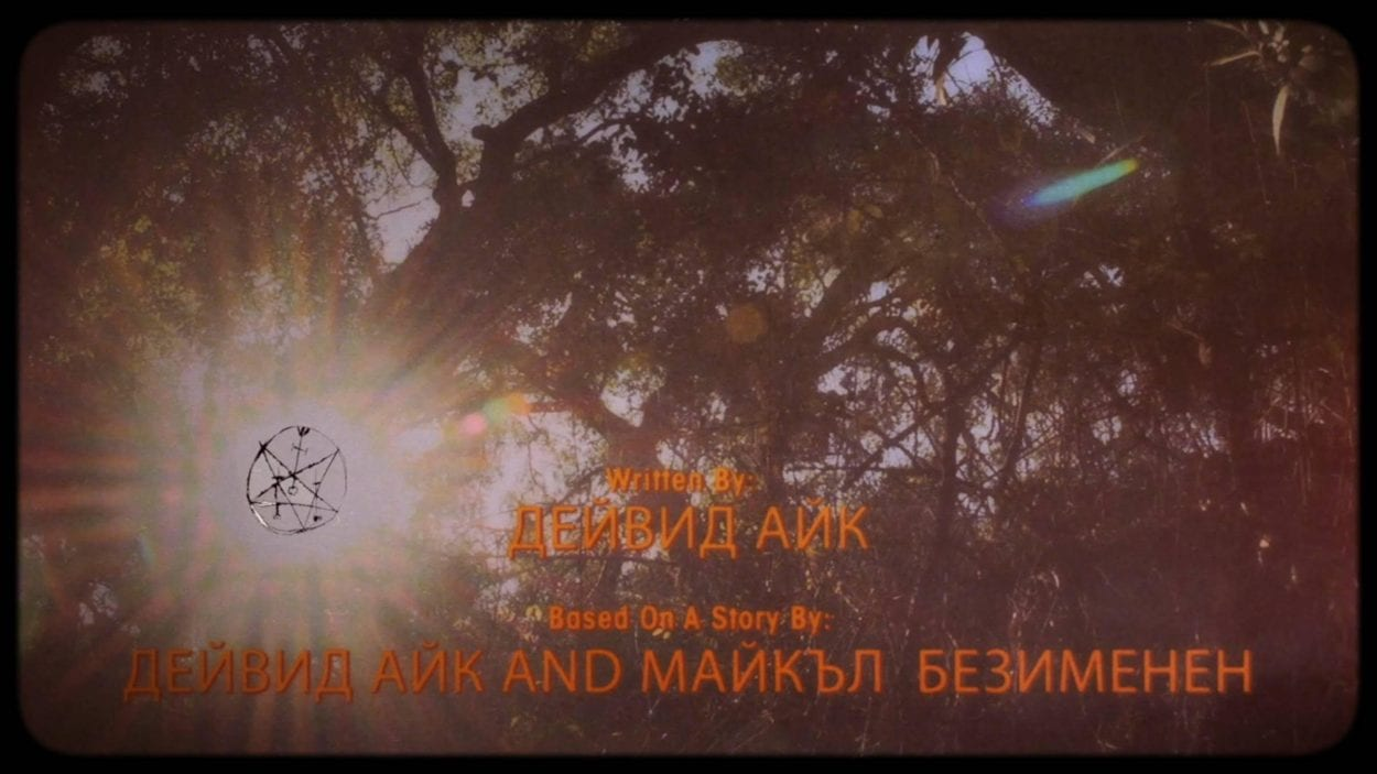 Screenshot looking up through the crossed branches of trees in forest. Their are russian film credits in yellow along the bottom of the screen. The sun shines through a gap in the branches and an occult sigil is laid over the film where the sun is seen.